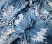 Heap of torn and frayed, threadbare jeans — Stock Photo