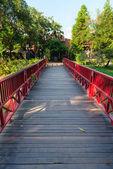 Wooden bridge with red fence in green park — Foto de Stock