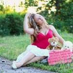 Beautiful blonde girl sitting on the green grass — Stock Photo
