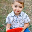 Caucasian little boy eats a slice of watermelon — Stock Photo