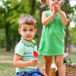 Caucasian little boy and girl eating sweets — Stock Photo