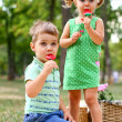 Caucasian little boy and girl eating sweets — Stock Photo #12760321