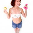 Young woman with dumbbells and cake — Stock Photo