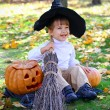 Little smiling boy with halloween pumpkins, a broom and a hat — Stock Photo