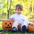 Stock Photo: Little boy with halloween pumpkins