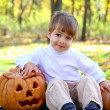 Royalty-Free Stock Photo: Portrait of a little smiling boy with two halloween pumpkins in