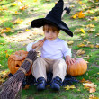 Little boy with halloween pumpkins, a broom and a hat — Stock Photo