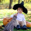 Little smiling boy with two halloween pumpkins, a broom and a ha — Stock Photo