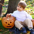 Little smiling boy with two halloween pumpkins and a broom sitti — Stock Photo