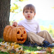 Little boy with halloween pumpkin and a broom sitting near a tre — Stock Photo