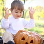 Portrait of a rapturous little boy with halloween pumpkin — Stock Photo #13927009