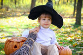 Portrait of a little boy with halloween pumpkins, a broom and a — Stock Photo
