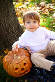 Happy little boy with halloween pumpkin sitting near a tree — Stock Photo