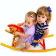 Two cute babies riding on a toy wooden horse isolated on white b — Stock Photo