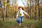 Little girl running with a bucket outdoors — Stock Photo