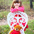 Girl with a teddy bear and a chair in the autumn forest — Stock Photo