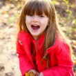 Little happy girl with leaves in autumn forest — Stock Photo