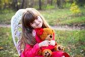 Little girl with a teddy bear in the autumn forest — Stock Photo