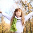 Little girl with hands up in the autumn forest — Stock Photo