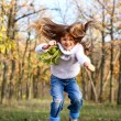 Happy little girl jumping from a chair outdoors — Stock Photo