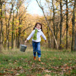 Sweet girl running with a bucket outdoors — ストック写真