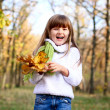 Happy little girl with maple leaves in autumn forest outdoors — Stock Photo