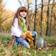 Girl with yellow leaves and a bucket outdoors — Stock Photo
