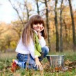 Little girl with a tin bucket in the autumn forest outdoors — Stock Photo