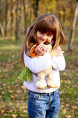 Little girl with teddy dog in autumn forest — Stock Photo