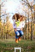маленькая девочка прыгает от стула на открытом воздухе — Стоковое фото