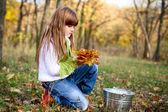 Chica seria en el bosque otoñal con hojas y un cubo superarse — Foto de Stock