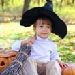 Little boy with halloween pumpkins, a broom and a hat in the aut — Stock Photo #14835143