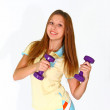 Smiling young woman with purple dumbbells in shorts isolated on — Stock Photo #14835325