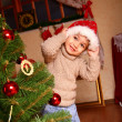 Happy little boy in a cap of Santa Claus standing near a Christm — Stock Photo