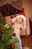 Glad liten pojke i en mössa av jultomten står nära en julstämning — Stockfoto