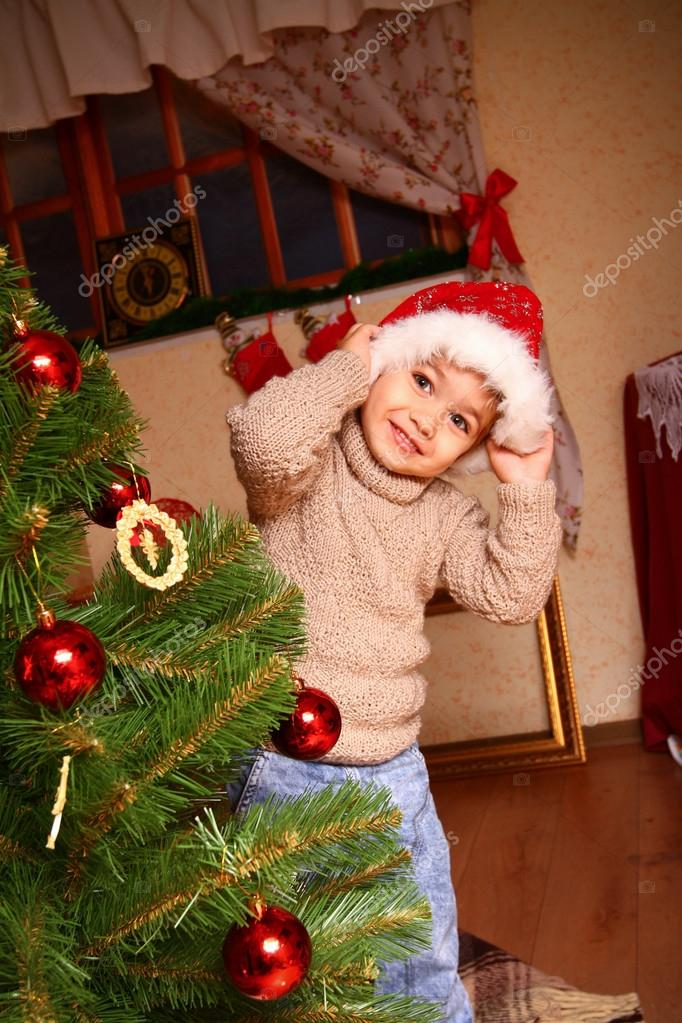 Happy little boy in a beige sweater and hat of Santa Claus standing near a Christmas tree in front of the window — Stock Photo #15631985