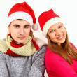 Smiling boy and girl wearing Santa Claus hats isolated on white — Stock Photo