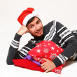Brunet guy lying with pillows wearing Santa Claus hat isolated o — Stock Photo