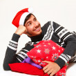 Smiling young man wearing a Santa Claus hat with pillows isolate — Stock Photo