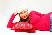 Cute girl with a cap and a pillow lying isolated on white backgr — Stock Photo