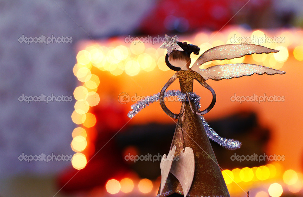 Christmas angel on the background of luminous garland, fireplace and firewood  Stock Photo #15849703