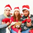 Young men and woman with Santa Claus hats, scarves, ball and pil — Stock Photo