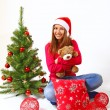 Smiling little girl sitting near a Christmas tree with a teddy b — Stock Photo