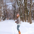 Smiling blond girl playing on the snow in a winter park outdoors — Stock Photo
