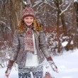 Stock Photo: Smiling girl playing with snow outdoors