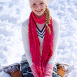 Portrait of girl sitting on the snow — Stock Photo