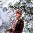 Laughing girl near pine trees in a winter park outdoors — Stockfoto