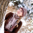 Smiling winter girl looking at a tree outdoors — Stock Photo