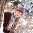Portrait of a smiling girl near a tree in a winter park outdoors — Stock Photo