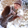 Cute girl playing with snow in a winter park outdoors — Stockfoto